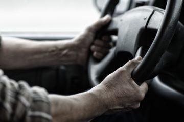 Mani di un uomo alla guida di un camion
