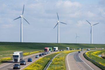 autostrada con mulini a vento sullo sfondo macchine e camion sulla strada